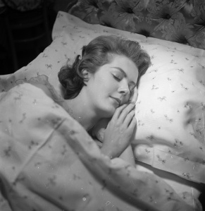 30th August 1957: A serene looking woman falls asleep on a matching pillowcase and duvet cover from Harrods department store in London. (Photo by Chaloner Woods/Getty Images)